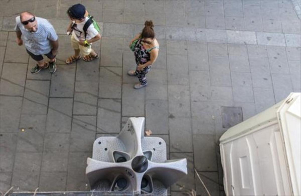 Unos turistas observan el reguero de orines que cae desde los urinarios colocados en la calle de Fusina.