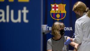 Una mujer se vacuna en el centro de inoculación situado en las instalaciones del Barça, este jueves.