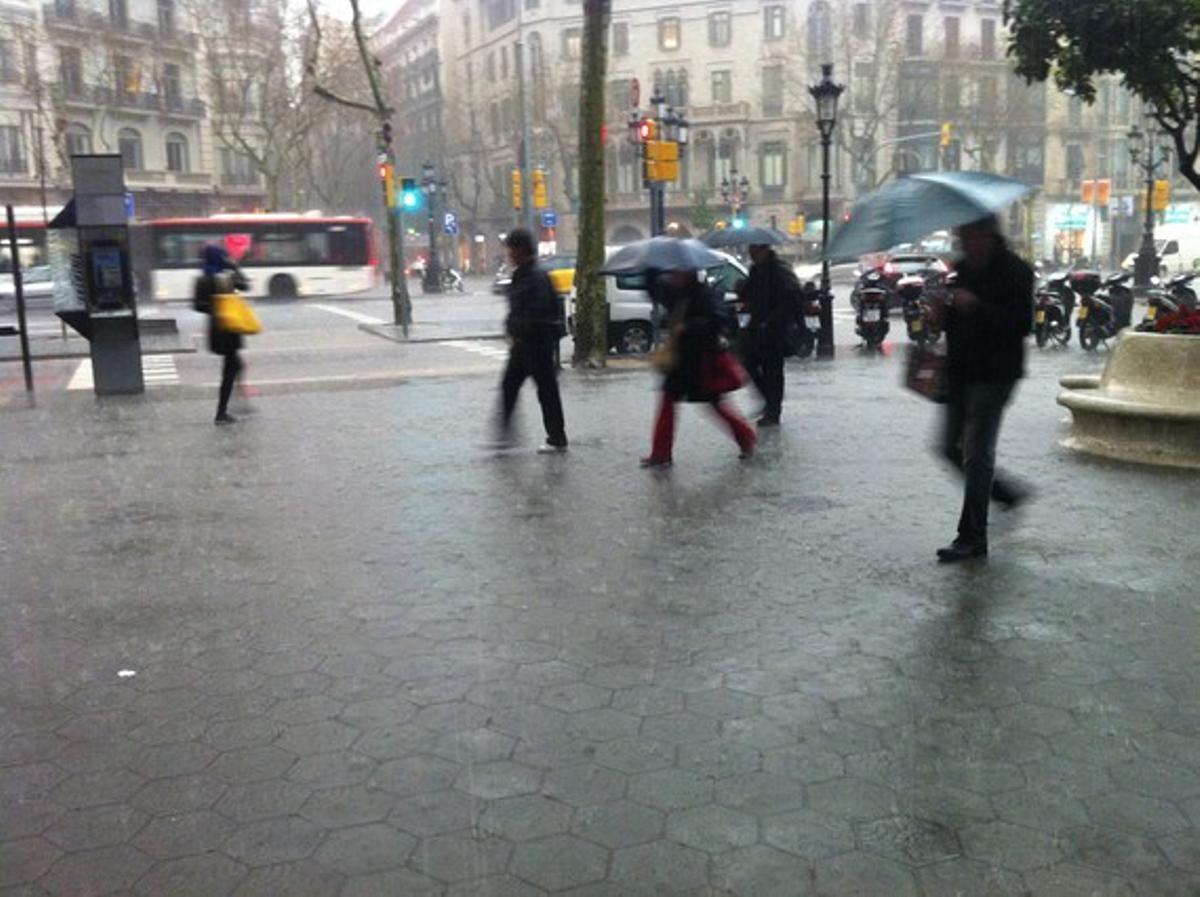 Transeúntes refugiándose de la lluvia en el paseo de Gràcia.