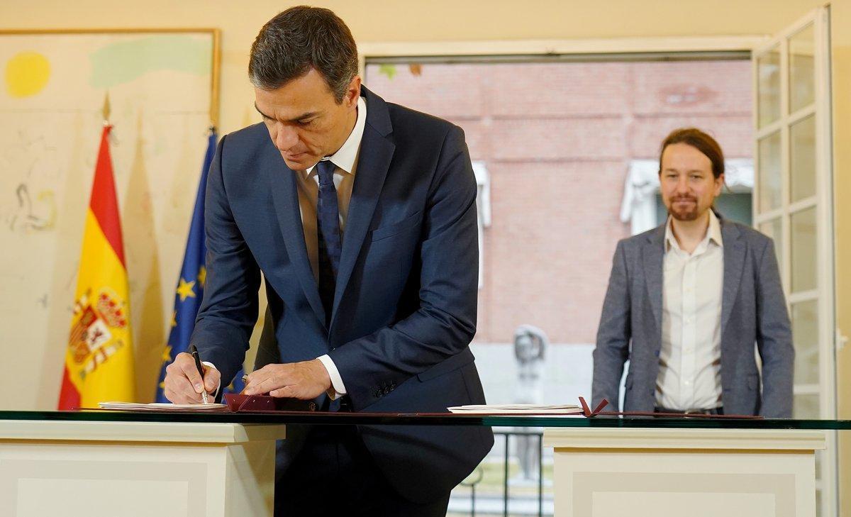 Pedro Sánchezfirma el acuerdo presupuestario ante la mirada de Pablo Iglesias, en la Moncloa.