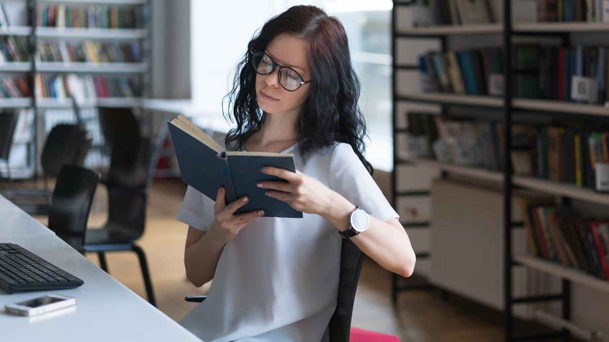 Una chica lee en una biblioteca.