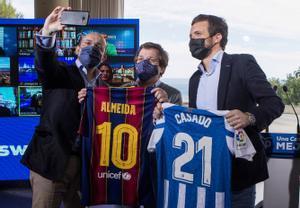 El presidente del PP, Pablo Casado, posa para un selfi junto al candidato del PPC a la Generalitat, Alejandro Fernández, y el alcalde de Madrid, José Luis Martínez-Almeida, con las camisetas del FC Barcelona y el RCD Espanyol, tras un acto celebrado este domingo en Badalona.