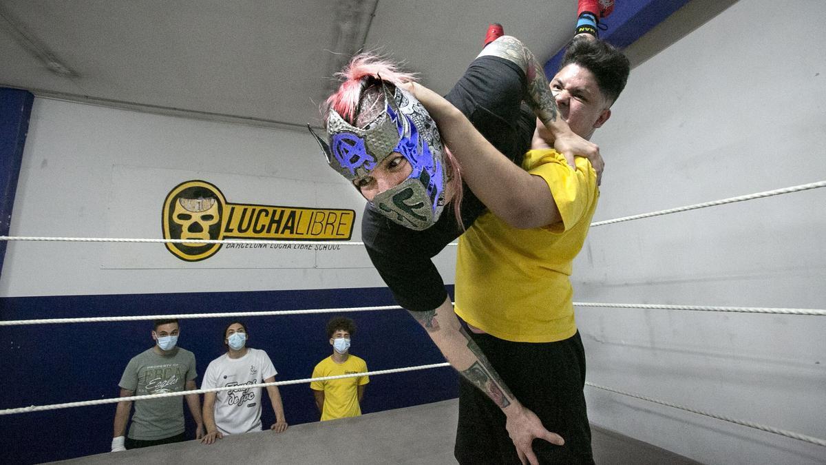 Jeffrey Pac y Anarko Montaña (con máscara), luchador chileno de visita, pelean en el ring de la escuela Lucha libre Barcelona delante de tres alumnos.