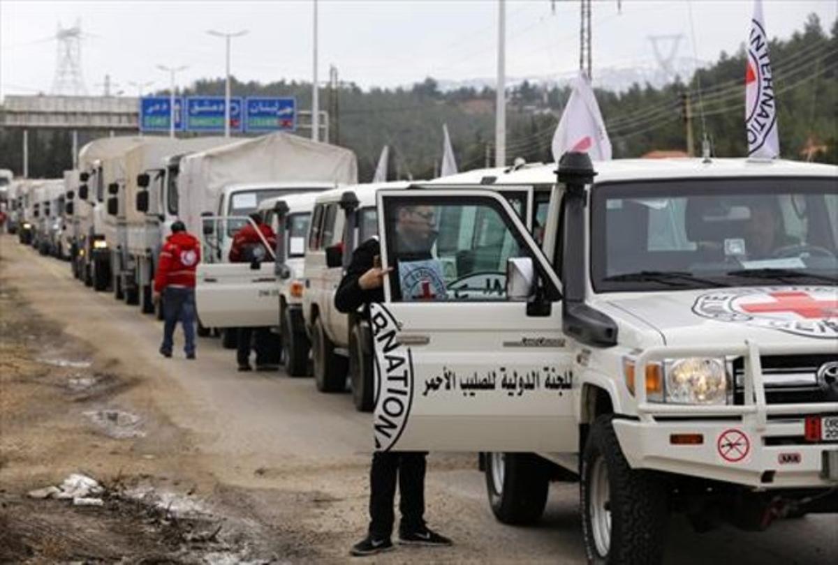 Vehículos con ayuda humanitaria esperan a entrar en la población siria de Madaya.