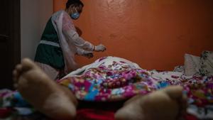 Un profesional del Centro Emisor de Actas de Defunción (CEDO) realiza la prueba del covid-19 a un hombre que falleció en su domicilio en Manaos.