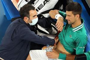 Djokovic es atendido por uno de los fisios del torneo.