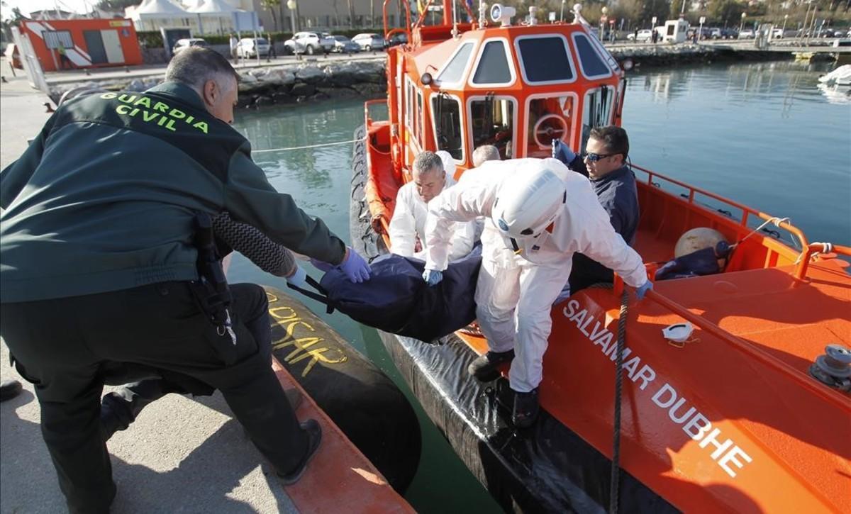 Agentes de la Guardia Civil y de Salvamento Maritimo trasladan el cadáver de uno de los inmigrantes fallecidos en aguas del Estrecho.