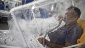 AME1175. MANAOS (BRASIL), 20/05/2020.- Profesionales de la salud ayudan este miércoles a un paciente de COVID-19 en el Hospital Municipal de Campaña Gilberto Novaes, en la ciudad de Manaos, Amazonas (Brasil). El hospital tiene dos unidades de cuidados intensivos, dos unidades de cuidados intermedios y 17 salas y está actualmente a su máxima ocupación. EFE/ RAPHAEL ALVES
