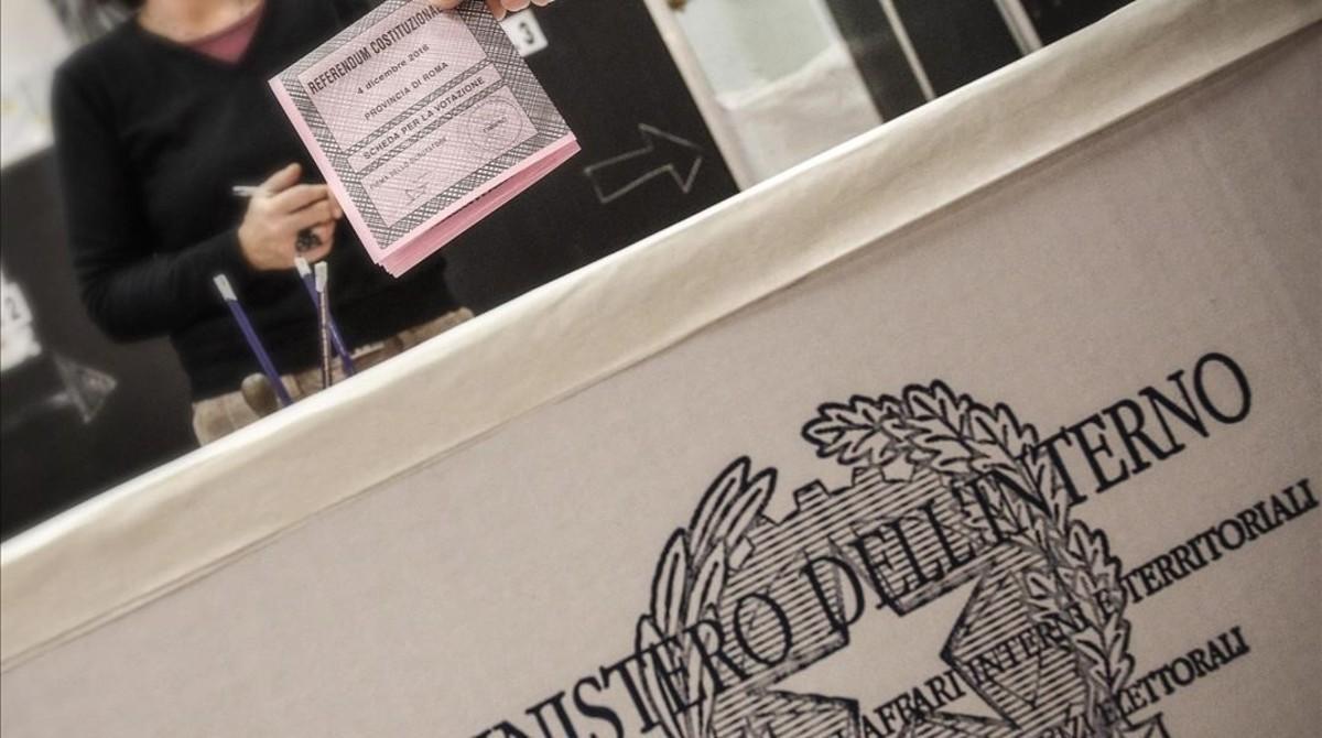 Un italiano anónimo introduce su papeleta en un centro electoral en Roma, este domingo.
