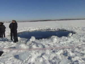 Varios hombres, junto a un agujero de ocho metros causado por el impacto del meteorito en un lago congelado de Cheliábinsk.