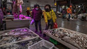 Dos mujeres compran pescado en un mercado de Wuhan, este viernes.