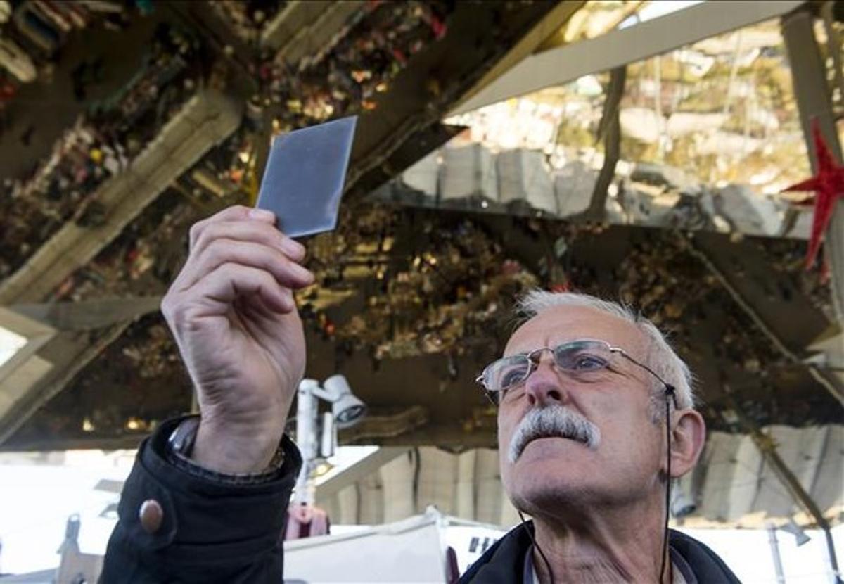 Enric Pareto, el resucitador defotografías antiguas, mira al trasluz un negativo de cristal en los Encants.