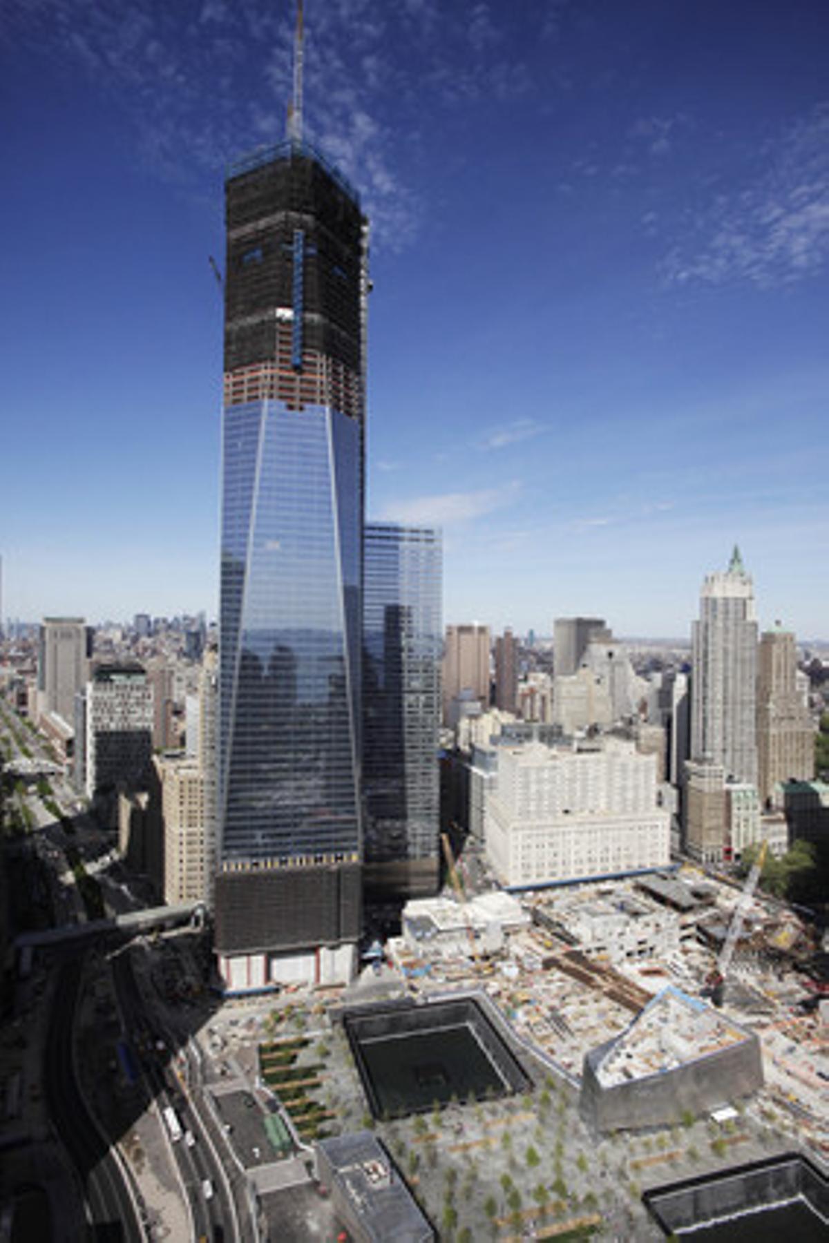 La Torre 1 del World Trade Center, ahora más alta que el Empire State, se levanta sobre el Memorial del 11 de Septiembre de Nueva York.