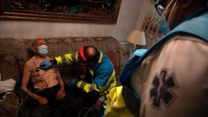 SUMMA 112 (Medical Emergency Services of Madrid) doctor Juan Jose Fernandes attends to an elderly man at his home in Madrid on November 6, 2020. - The novel coronavirus has killed at least 1,255,803 people since the outbreak emerged in China last December, according to a tally from official sources compiled by AFP on November 9. (Photo by PIERRE-PHILIPPE MARCOU / AFP)