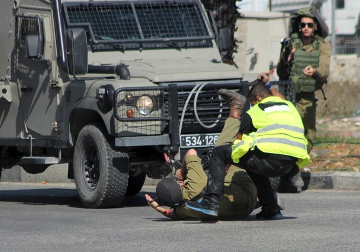 Momento en que un palestino disfrazado de periodista acuchilla a un militar israelí en Hebrón, este viernes.