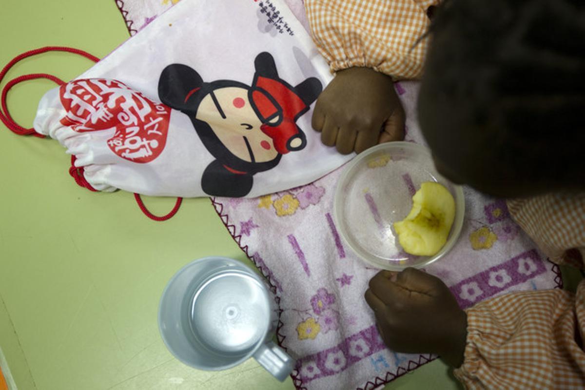 Una niña toma fruta en la escuela de El Carmel, el viernes pasado.