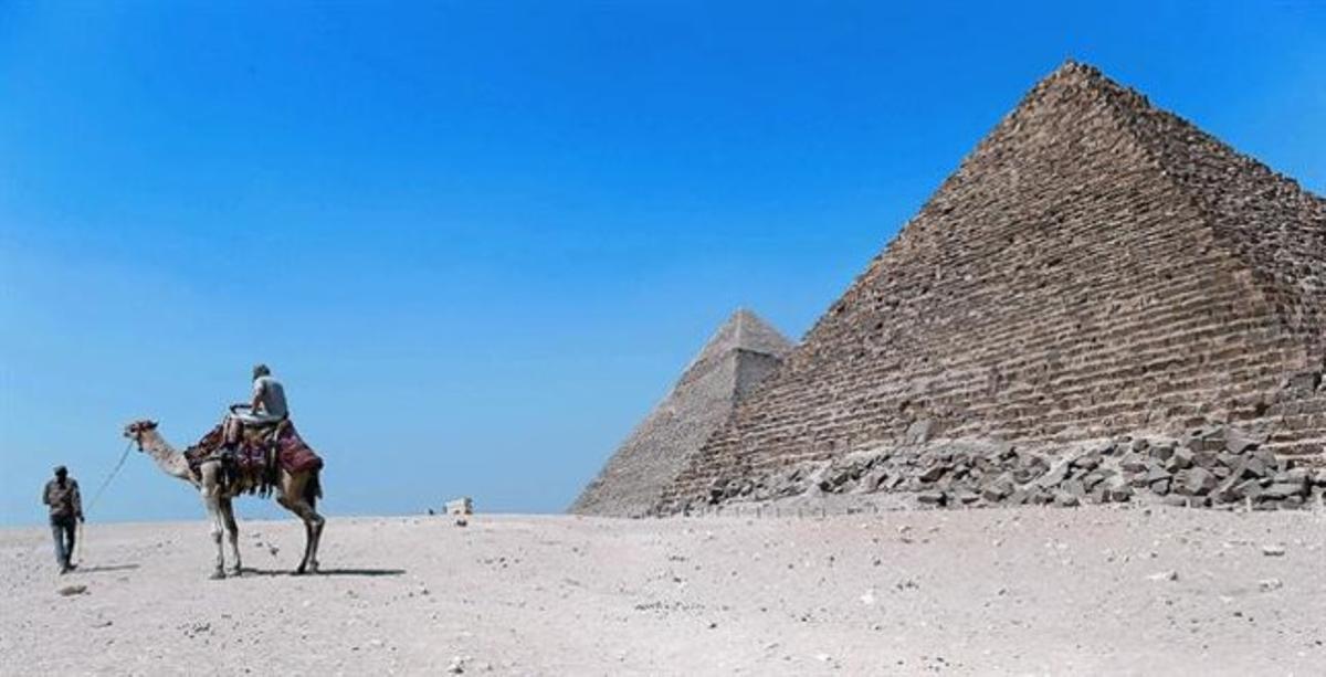 Un turista montado en un camello visita la zona de las pirámides de Gizah.