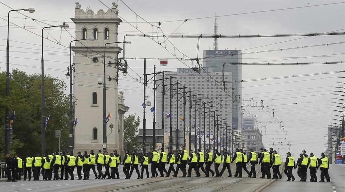Varios policías caminan hacia el estadio nacional donde se celebrará la cumbre.