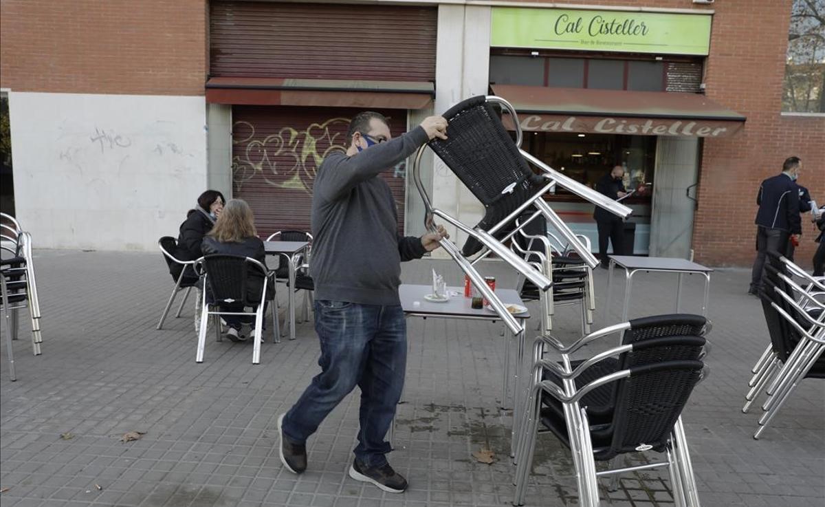 El propietario de un bar de Poblenou recoge las mesas al acabarse el tiempo para servir desayunos.