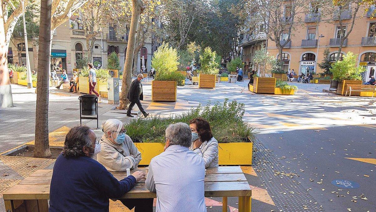 Ciudadanos conversando sentados en una de las mesas de la supermanzana de Sant Antoni.