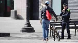 Un ciclista pasa junto a un agente de la Guardia Urbana cerca de la plaza de Catalunya, esta semana