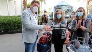 Unas turistas holandesas se frotan las manos con gel hidroalcohólico a su llegada al hotel de Maspalomas.