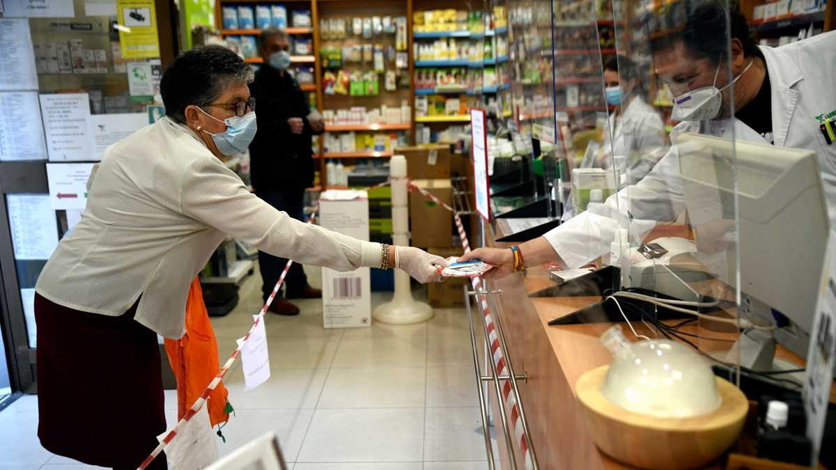 España suma 123 muertes por coronavirus en las últimas 24 horas. En la imagen, un farmacéutico entrega unas mascarillas a una clienta en una farmacia de Madrid.