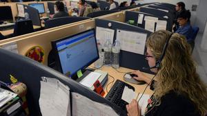 Una mujer atiende llamadas en su puesto de trabajo de atención al cliente