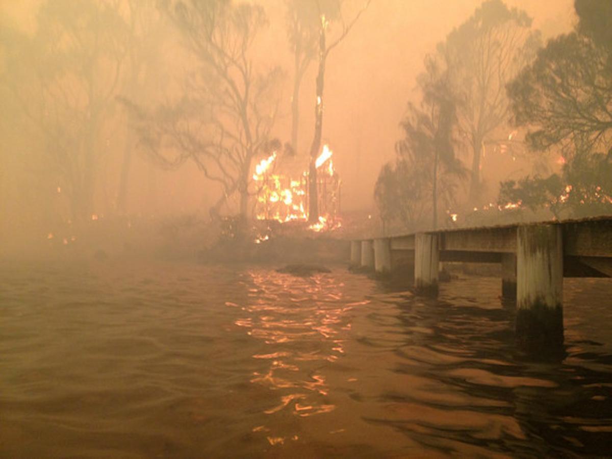 La casa de los Holmes, en llamas, al fondo, tras el embarcadero.