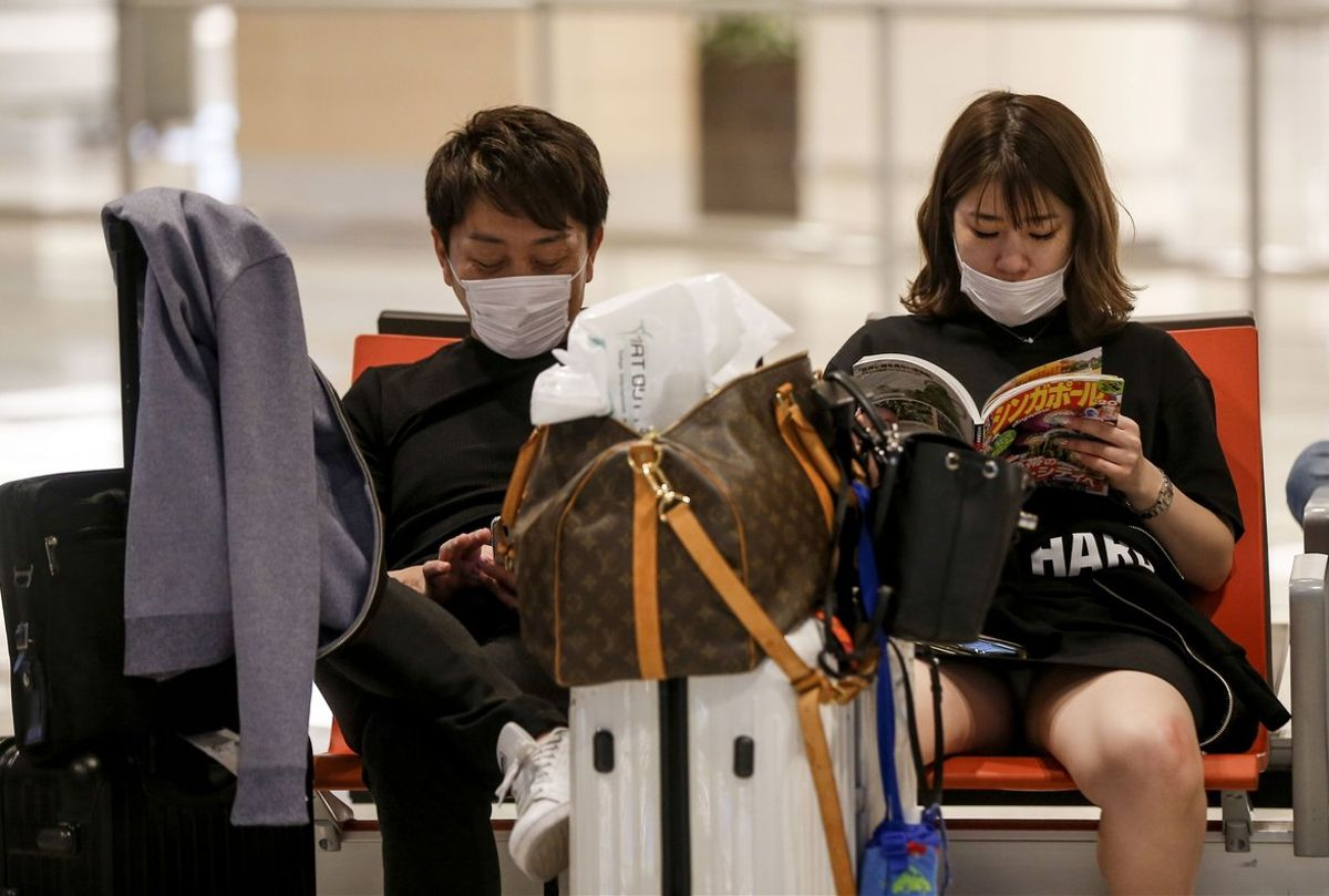 Singapore (Singapore), 09/02/2020.- A couple wear protective masks at the arrival hall of Changi Airport in Singapore, 09 February 2020. Singapore's Ministry of Health has reported 40 cases of the novel coronavirus (2019-nCoV). The Ministry of Health has raised its Disease Outbreak Response System Condition (DORSCON) level from yellow to orange, meaning that additional precautions will be taken such as increased temperature screening and the cancellation of group activities in schools and the community. (Singapur, Singapur) EFE/EPA/WALLACE WOON