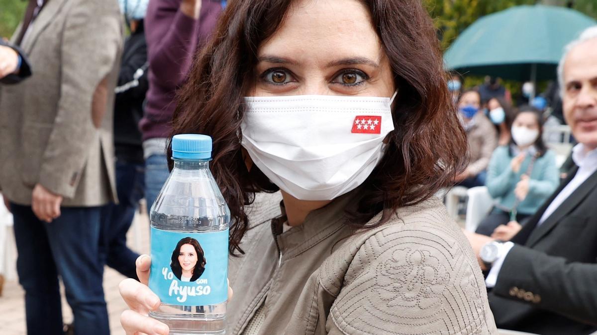 Isabel Díaz Ayuso posa con una botella de agua con su cara impresa durante un acto de campaña celebrado en Pozuelo de Alarcón.
