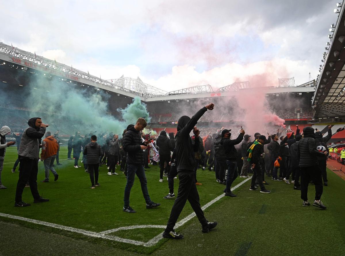 Los seguidores del United, en el césped de Old Trafford.