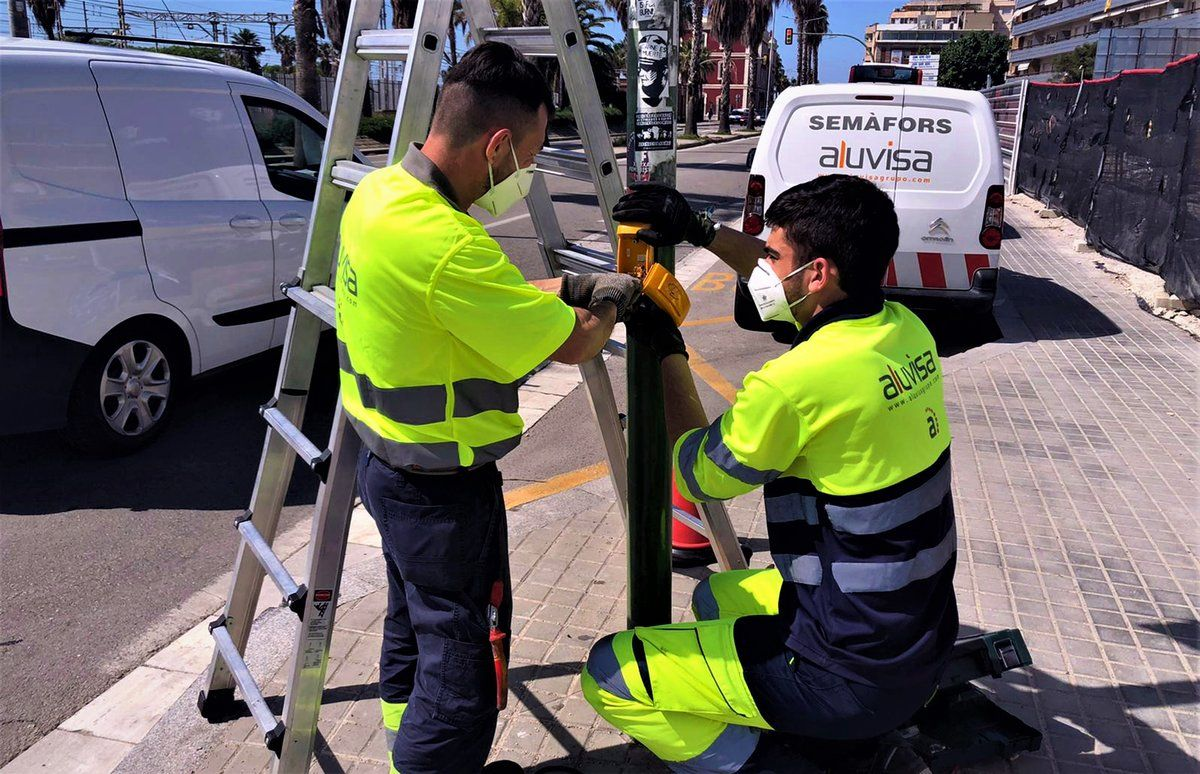 Operarios cambian la botonera de un semáforo en la carretera N-II en Mataró.