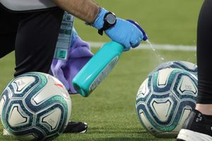 Un asistente desinfecta unos balones de fútbol antes de un partido.