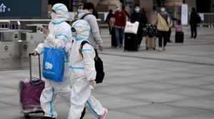 Pasajeros llegan a Wuhan protegidos con trajes.