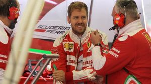 Sebastian Vettel dialoga con miembros del equipo Ferrari, en México.