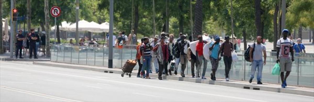 Grupos de manteros vigilados por agentes de losMossos en el centro de Barcelona.