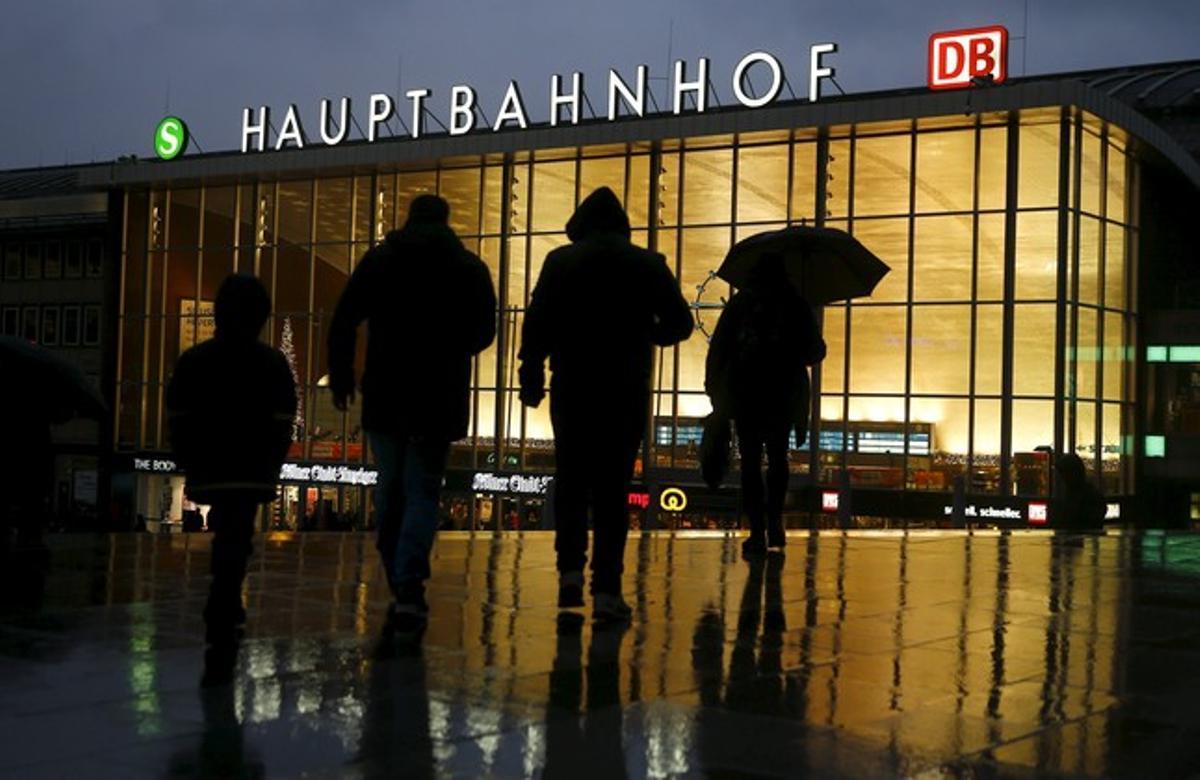 Un grupo de gente camina frente a la estación de tren de Colonia.