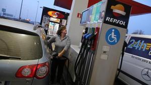 Una conductora carga combustible en una gasolinera.