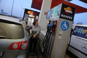 El IPC suma su novena tasa negativa tras subir en diciembre hasta el -0,5%. En la foto, una conductora reposta gasolina.