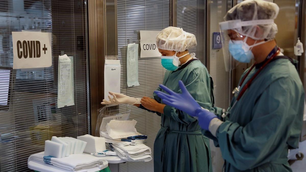 Dos profesionales sanitarios trabajan en la uci del Hospital Vall d'Hebron de Barcelona, este miércoles.