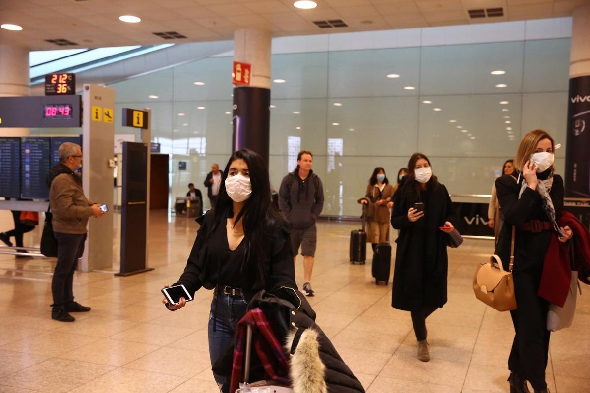 Pasajeros saliendo de un vuelo de Milán,en el aeropuerto de El Prat,con mascarillas por el Coronavirus Covid 19