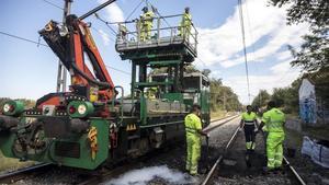 Operarios de ADIF y COMSA reparando la catenaria, en el punto kilometrico 191, en Caldes de Malavella.