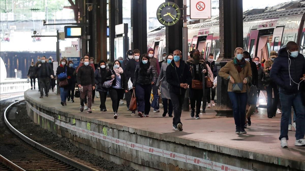 Los viajeros, que usan máscaras faciales protectoras, caminan en una plataforma en la estación de tren de Saint-Lazare en París