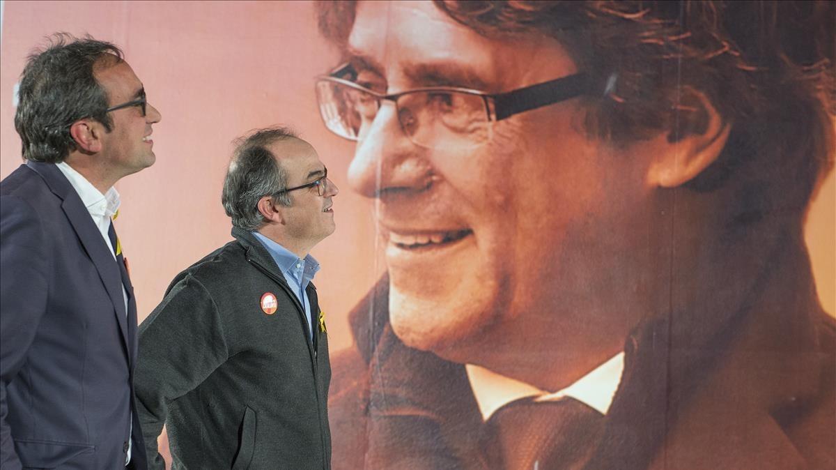Jordi Turull y Josep Rull ante el cartel electoral de Carles Puigdemont
