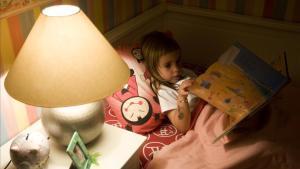 Una niña, en su habitación, a punto de ir a dormir.