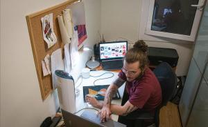 Un joven ilustrador teletrabaja desde su casa para un estudio de diseño gráfico en Barcelona.