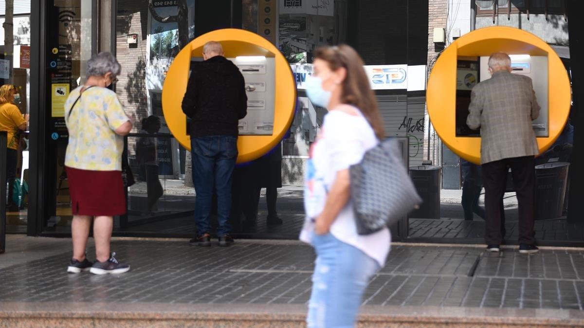 Varias personas sacan efectivo en un cajero en una oficina bancaria en Barcelona.