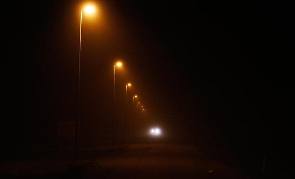Un vehículo se desplaza este domingo por la pequeña población islandesa de Kirkjubaejarklaustur en mitad de la niebla producida a raíz de la nube de ceniza expulsada por un volcán del país.