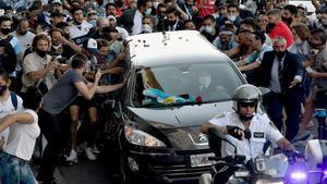 La multitud se agolpa ante el vehículo con feretro de Maradona.